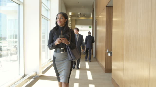 Tracking shot of a businesswoman walking down a corridor
