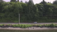 Tracking shot of a car driving next to a lake