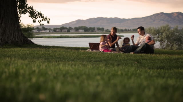 A tracking shot of a family of five eating sandwhiches as the have a picnic on a windy day.