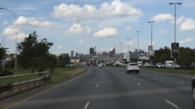 A tracking shot of a highway road driving towards the city center of Johannesburg In the background the cityscape can be seen