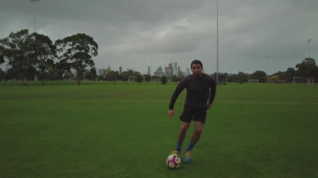 Tracking shot of a man training/playing soccer