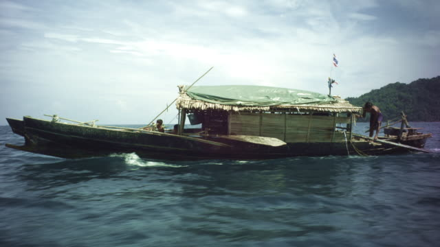 Tracking shot of a motorised fishing boat of the Moken people as it travels across the water in Thailand.