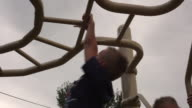 Tracking shot of a small boy hanging from monkey bars.