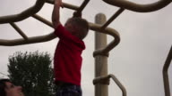 Tracking shot of a small boy hanging from monkey bars with help from his mother.