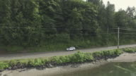 Tracking shot of a small SUV driving next to a lake
