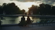 Tracking shot of a Tuileries Gardens fountain at sunset