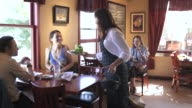 Tracking shot of a waitress serving food