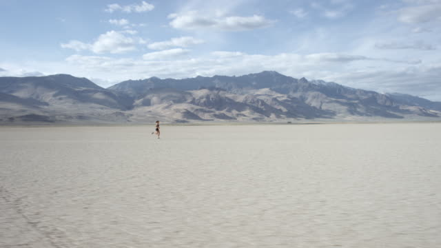 Tracking Shot of a Woman Running in the Desert