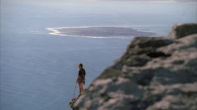 Tracking shot of a woman standing on the edge of a cliff looking out towards the sea and Robben Island