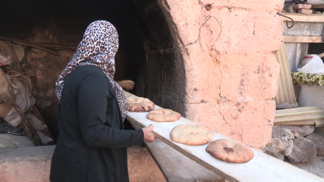 Tracking shot of a woman with fresh bread on a slab of wood NO