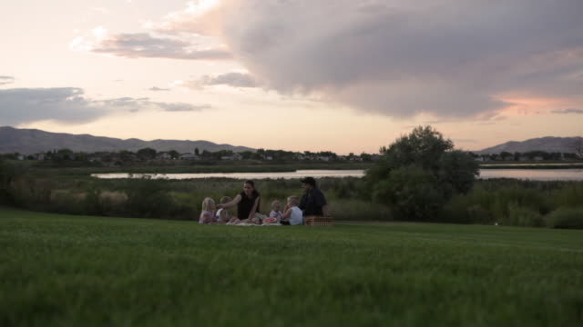A tracking shot of a young family having a picnic by a lake on a cloudy day.