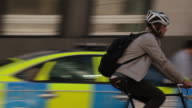 Tracking shot of a young man cycling near Liverpool Street Station, London, UK.