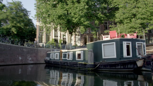 Tracking shot of buildings and houseboats along the Amsterdam Canal in Netherlands