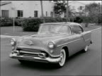 B/W 1954 tracking shot of Oldsmobile 88 driving past houses + palm trees on suburban street / Florida?