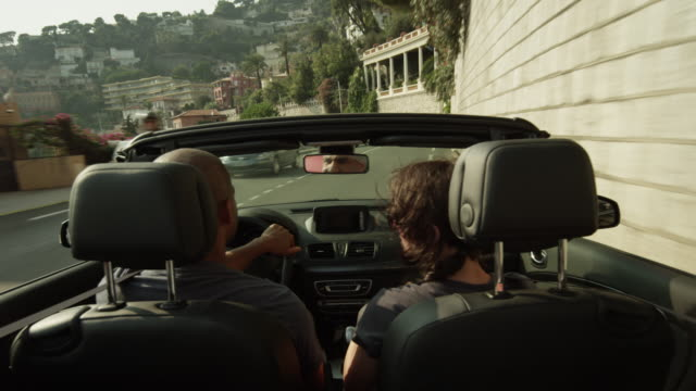 Tracking shot of people driving in convertible / Nice, France