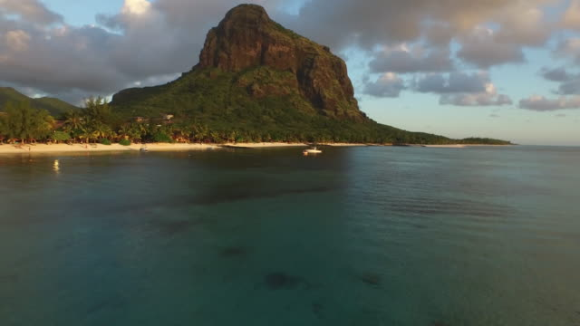 Tracking shot of sea and rocky mountain against cloudy sky, Mauritius