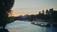 Tracking shot of the banks of the Seine river at sunset, boats passing by