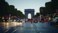 Tracking shot of the Champs-Elys��es avenue, french flags decorated, looking at the Arch of Triumph, at dusk