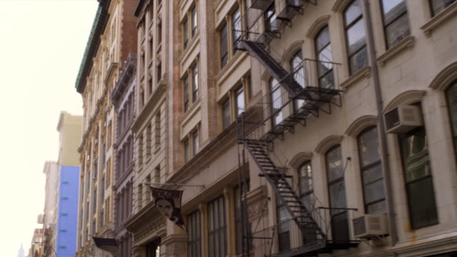 Tracking shot of the side of buildings with fire escapes.