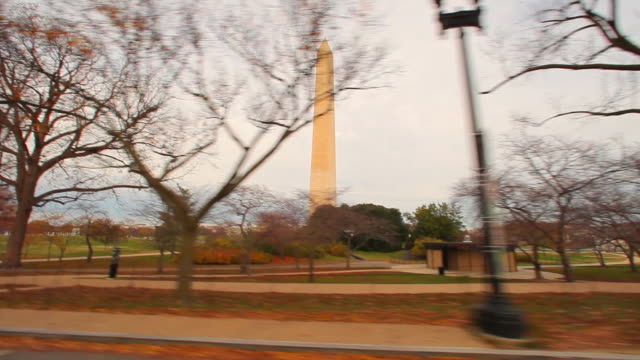 Tracking shot of the side of the Washington Monument with trees in foreground.