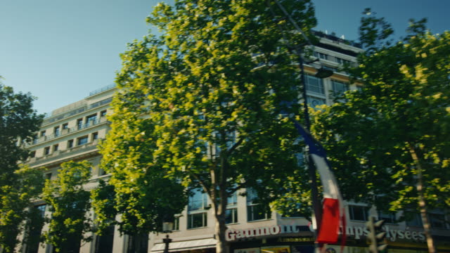 Tracking shot of the stone buildings surrounding the Champs-Elysées avenue, french flags