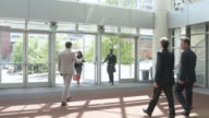 Tracking shot of two businessmen leaving a building