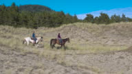 Tracking shot of two girls riding on horses
