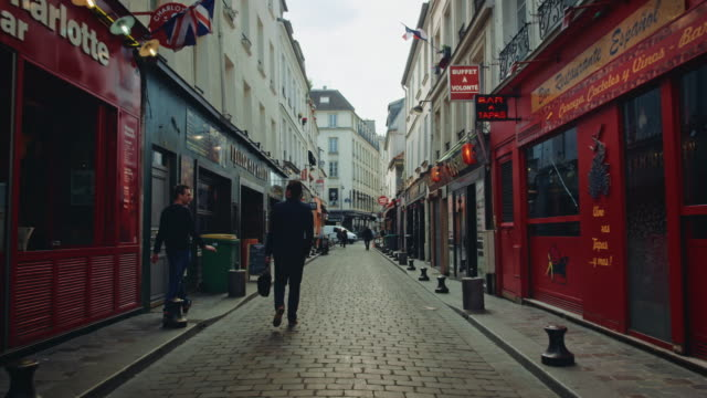 Tracking shot of typical Paris streets, with bars and cafés, people walking by