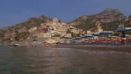Tracking shot of waves lapping Positano beach, Amalfi Coast, Italy