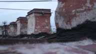 Tracking shot past a row of chimneys on a rooftop.