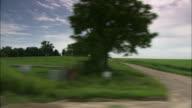 Tracking shot past green fields in Iowa.
