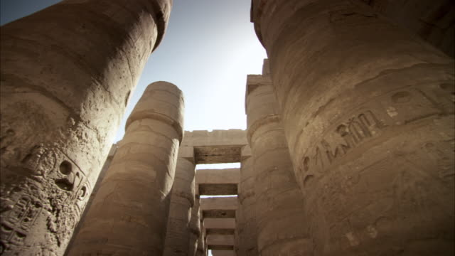 Tracking shot past the stone pillars of an ancient Egyptian temple.