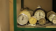 Tracking shot past various small clocks on a shelf.