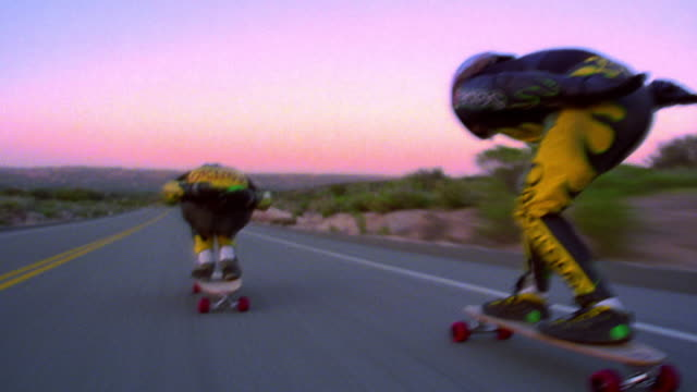 MS tracking shot REAR VIEW two skateboarders speeding on mountain road at sunset / slow down + signal to camera