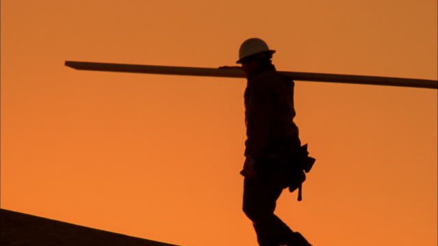 Tracking shot silhouette of construction worker carrying plank / Phoenix, Arizona