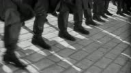 B/W MS tracking shot soldiers legs marching in unison