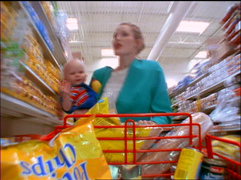 FAST tracking shot stressed businesswoman holding baby + pushing cart thru aisle of supermarket