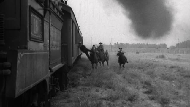 Tracking shot train robbers on horseback riding beside moving train and jumping onto train