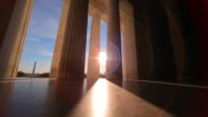 A tracking shot with a lens flare of the bottom of the pillars of the Lincoln Memorial.