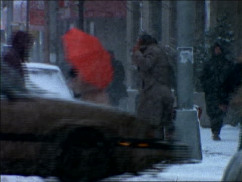 tracking shot woman with red umbrella crossing city street in snowstorm / New York City