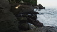 Tracking slow motion shot of heavy surf pounding on craggy boulders.