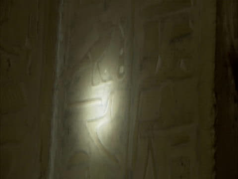 Tracking torchbeam down stone engraved with ancient Egyptian hieroglyphics, Sakkara, Egypt (sound available)