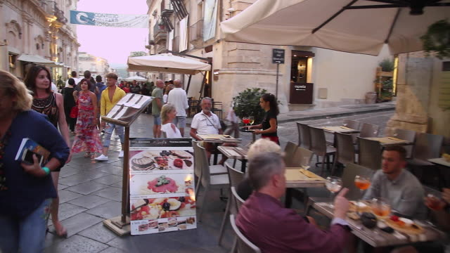 Tracking tourists and locals taking an early evening stroll along the beautiful streets of Noto, Sicily, Italy