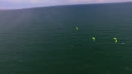 Tracking wide shot of 3 extreme sports kite surfers racing as they sail on the coast of Vietnam