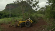 WS Tractor clearing brush at foot of steep mountain / Pantanal, Mato Grosso do Sul, Brazil