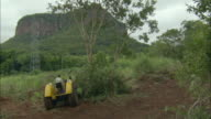 ZO WS Tractor clearing brush at foot of steep mountain / Pantanal, Mato Grosso do Sul, Brazil