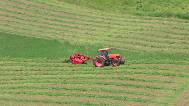 WS TS AERIAL POV Tractor harvesting grass in farmland / Davis County, Iowa, United States