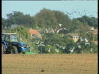 Tractor moves from left to right plowing muddy field. Birds fly off into air houses and trees in background Norfolk