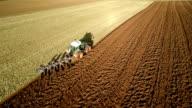 AERIAL : Tractor plowing Field