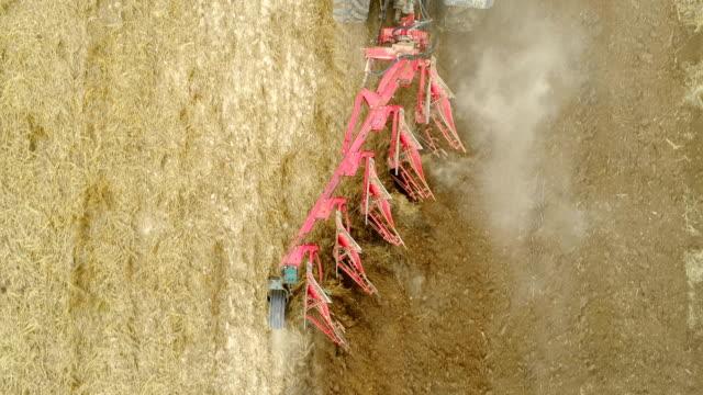 Tractor plowing field with harrows - 4K